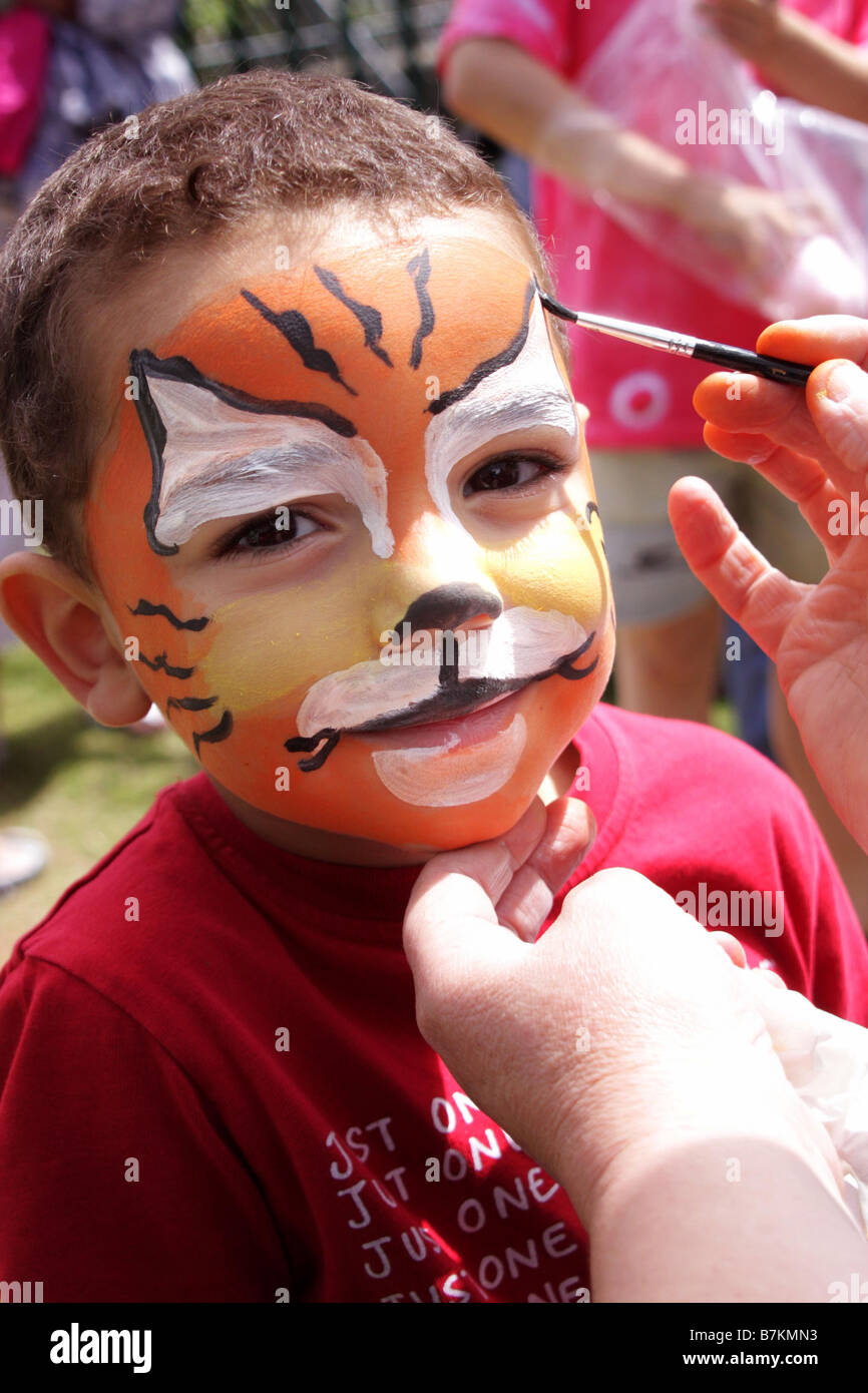 A young boy has his face painted at a summer fete in Oxfordshire - Stock Image