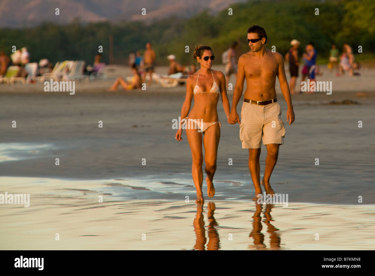 Young couple holding hands while walking along the beach at Playa Tamarindo, Costa Rica. - Stock Image