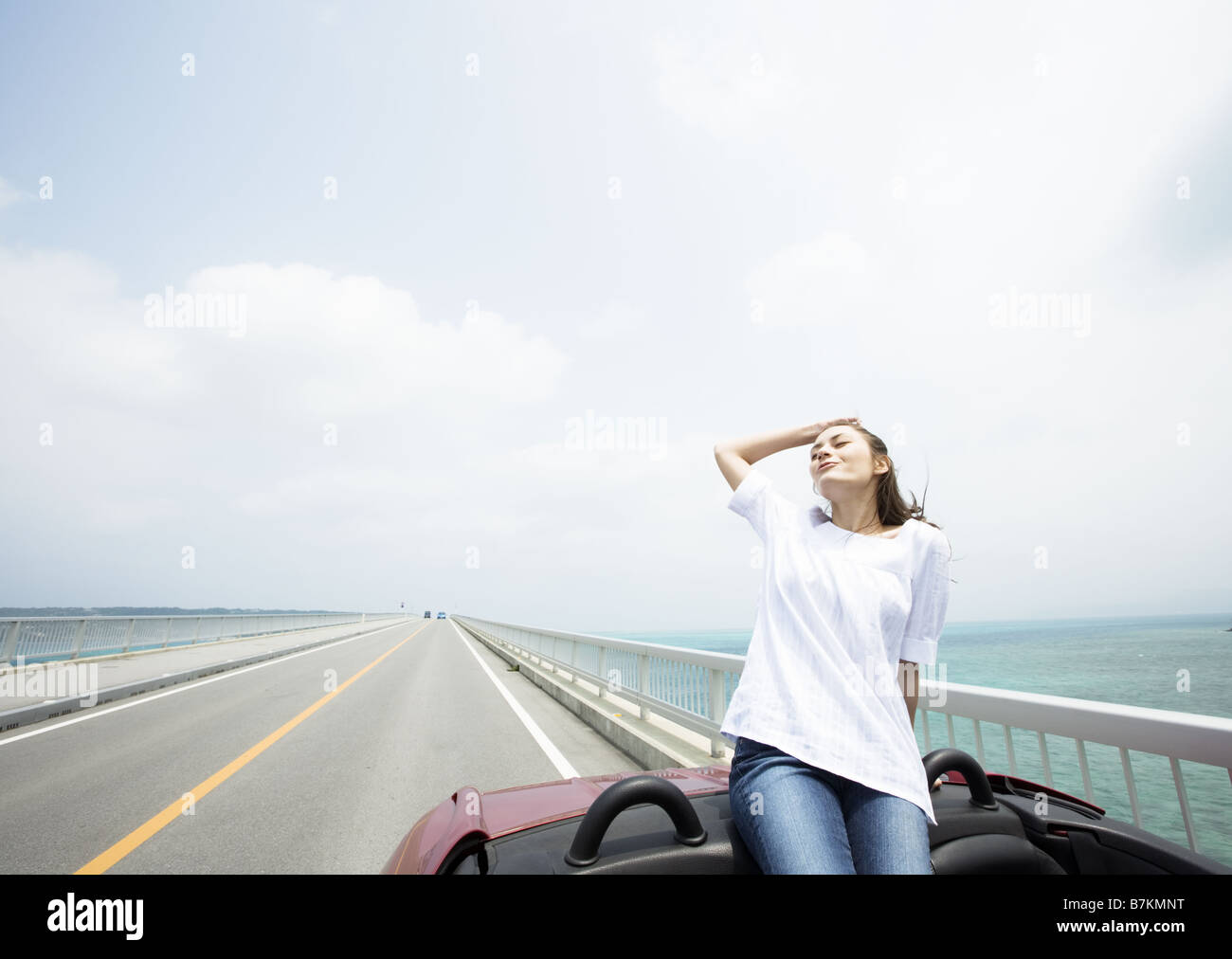 A young woman in a convertible - Stock Image