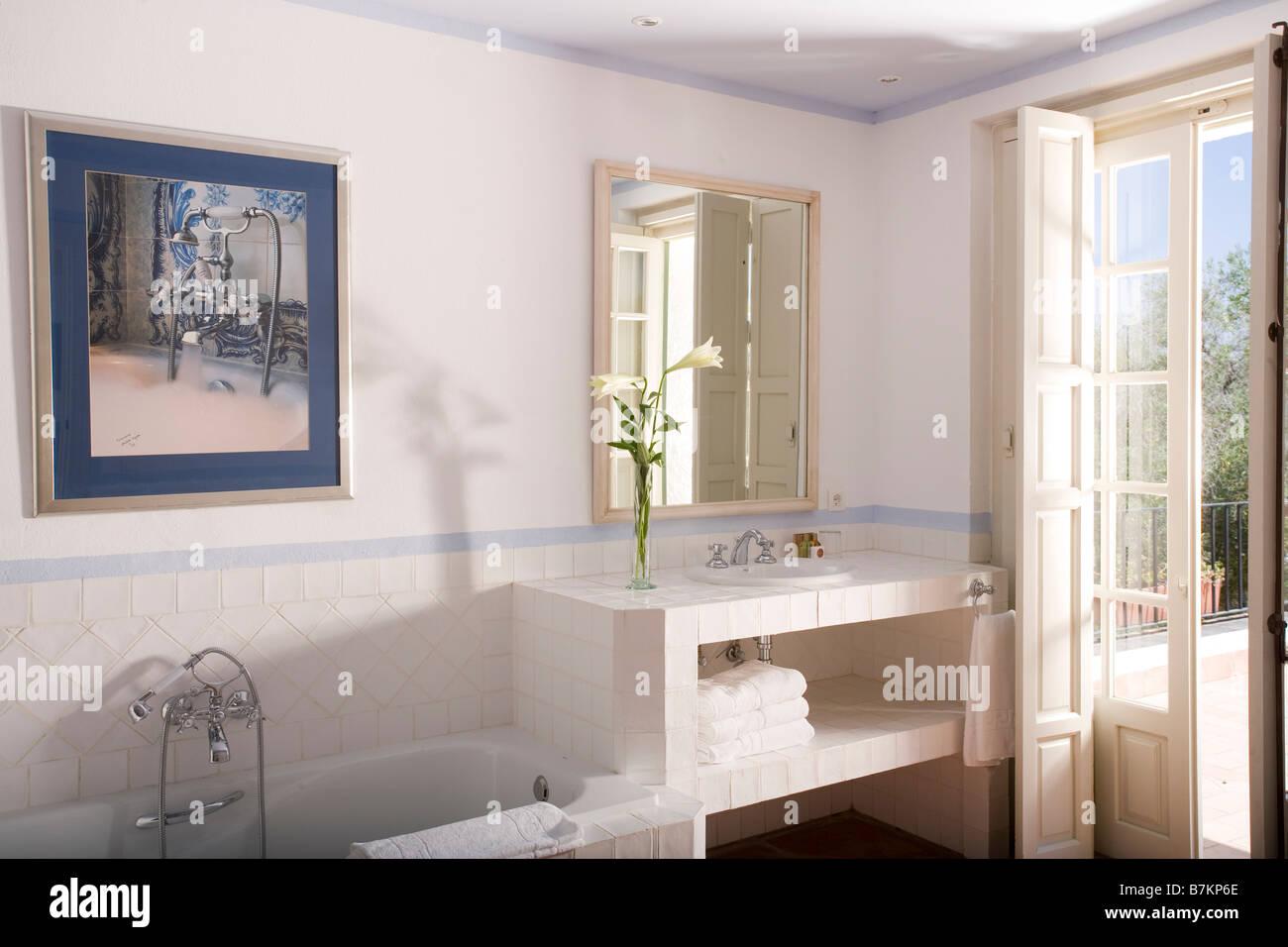 Basin In Simple Vanity Unit Beside French Doors In Modern White Hotel  Bathroom In Arcos De La Frontera In Southern Spain