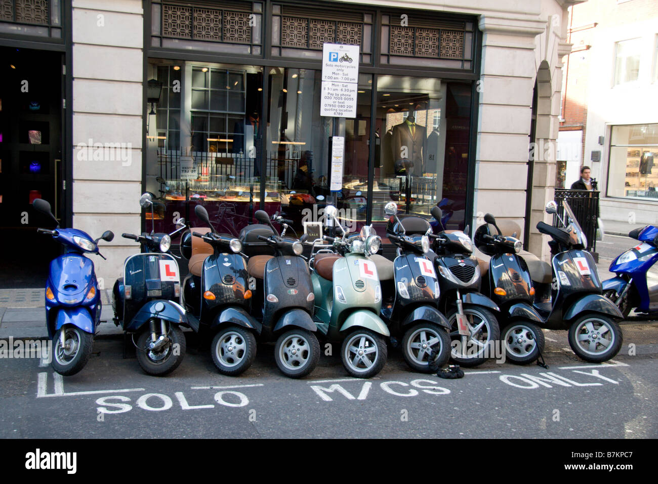 A row of motorcycle (mopeds) parked in a special parking zone on Saville Row, London. Jan 2009 - Stock Image
