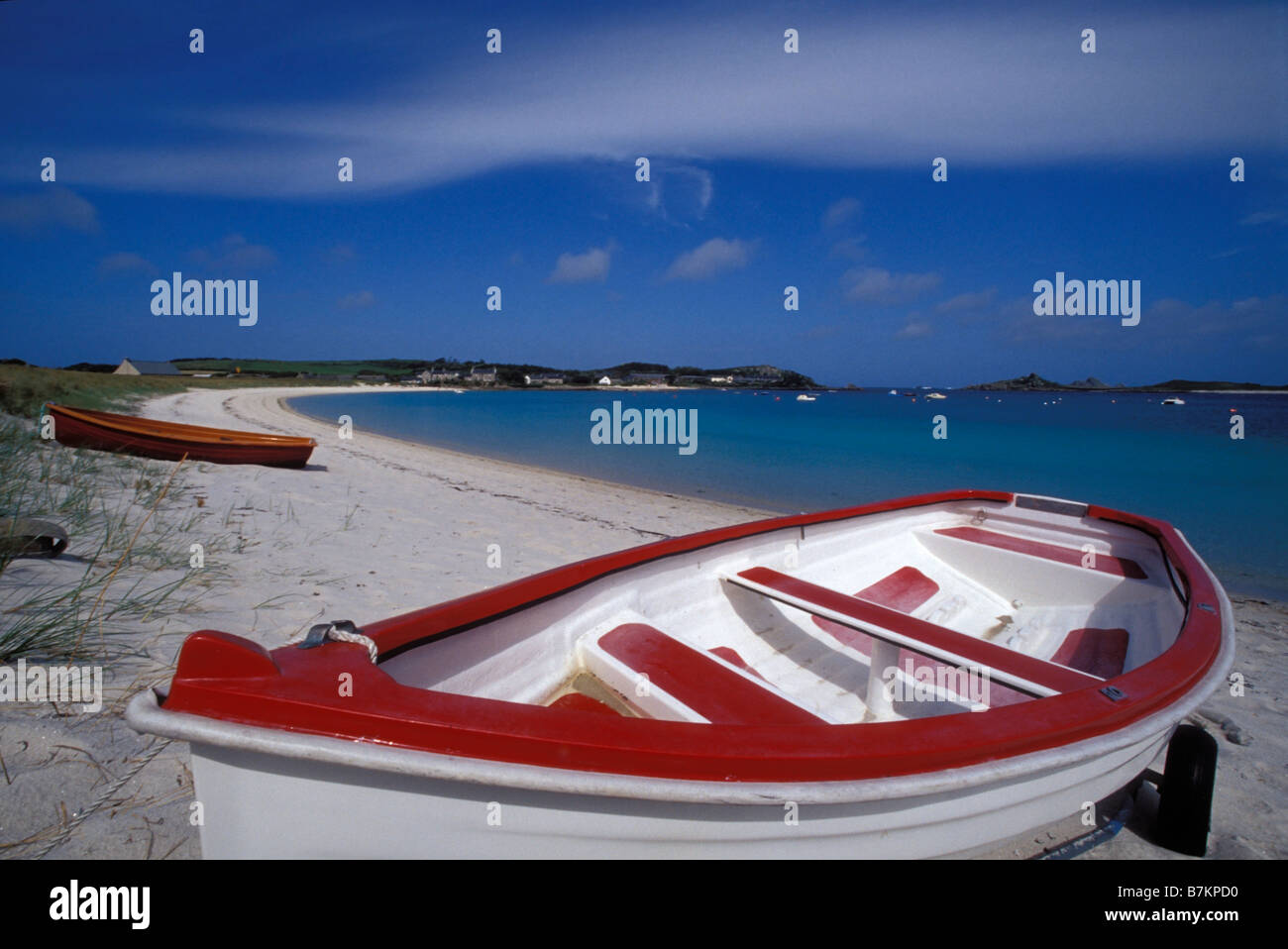 A pretty red and white rowing boat moored on the beach at Green Porth. Old Grimsby. Tresco, Isles of Scilly England - Stock Image