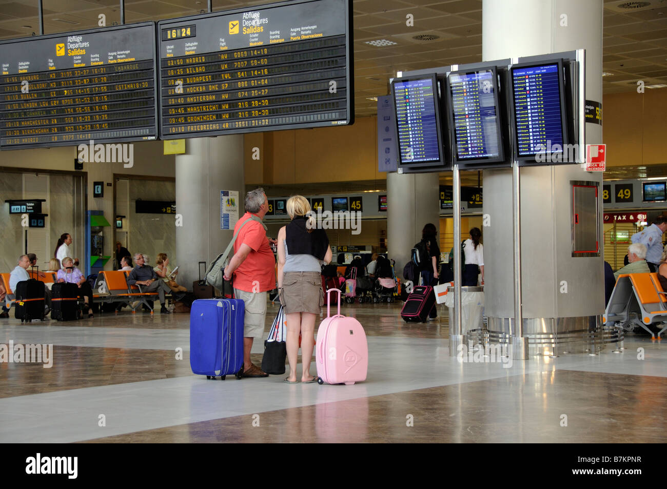 Airport terminal departures board travellers man woman at Reina Sofia Airport in southern Tenerife Canary Islands Stock Photo