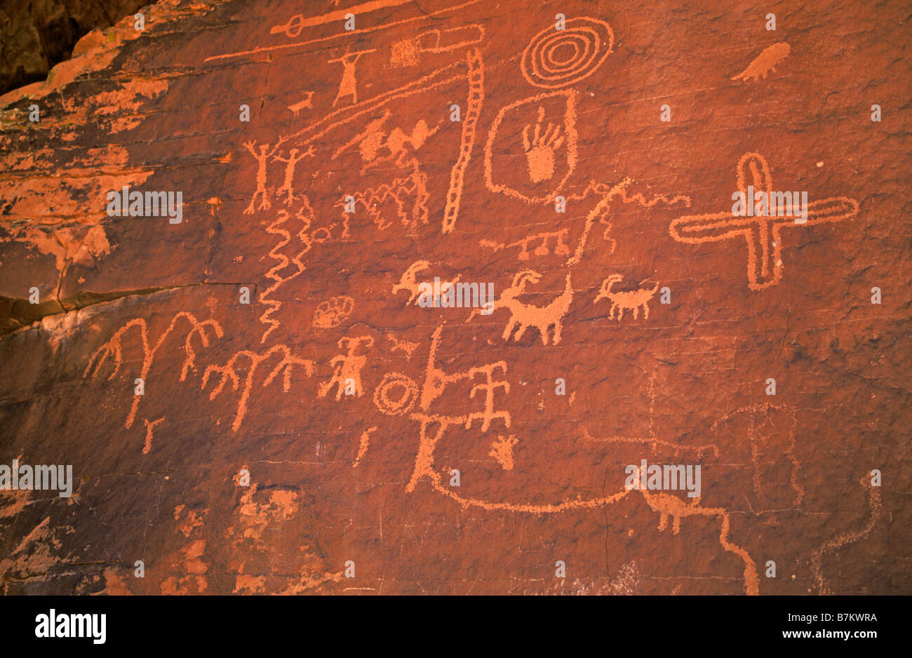 Ancient petroglyphs of people and bighorn sheep made by Anasazi orBasketmaker Indians on sandstone cliffs - Stock Image