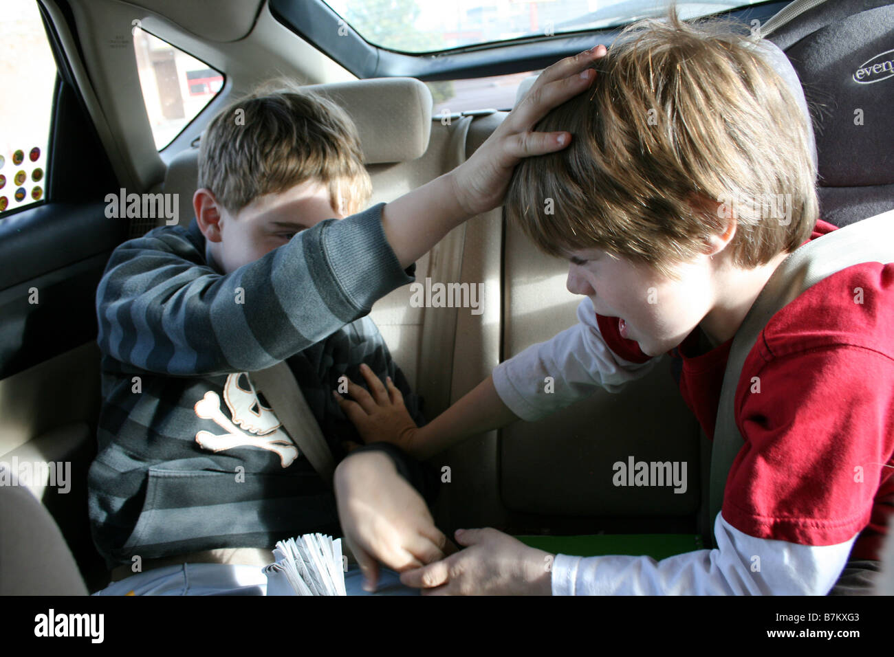 two brothers fighting with eachother in the back seat of car - Stock Image