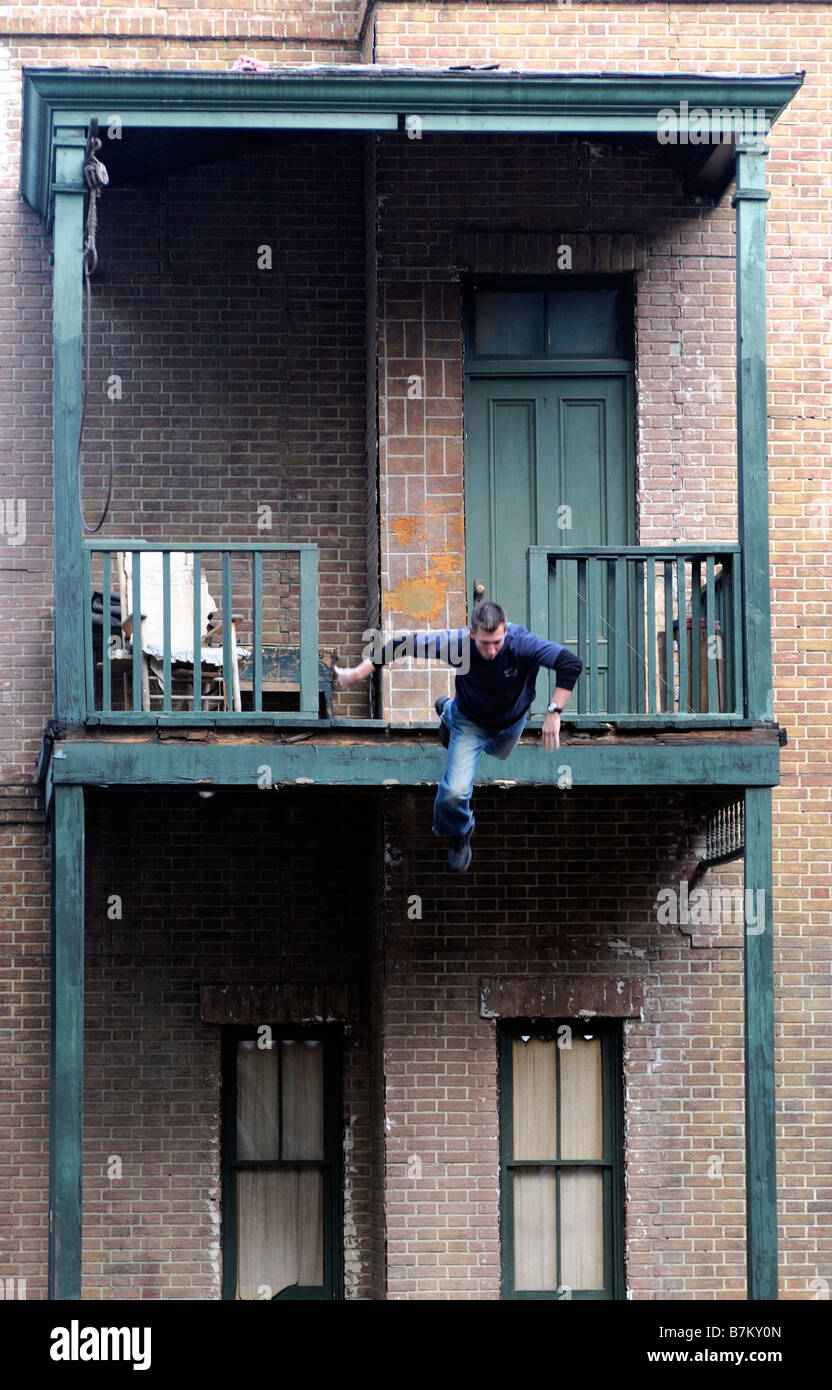 stunt man falling from an upstairs balcony on a movie film set universal studios tour backlot los angeles LA california - Stock Image