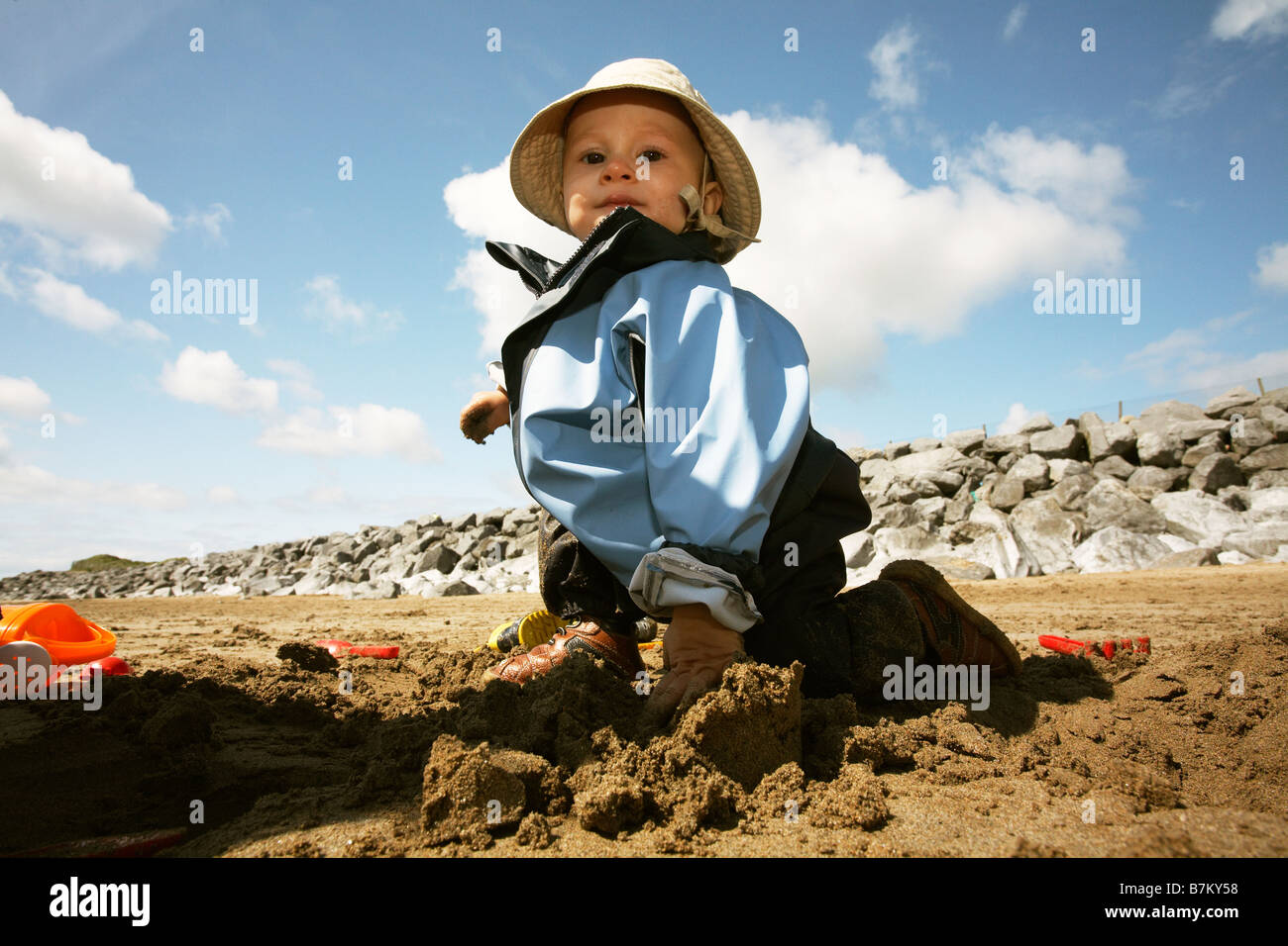Baby playing on beach in wet sand. Wearing cagoule and hat. - Stock Image