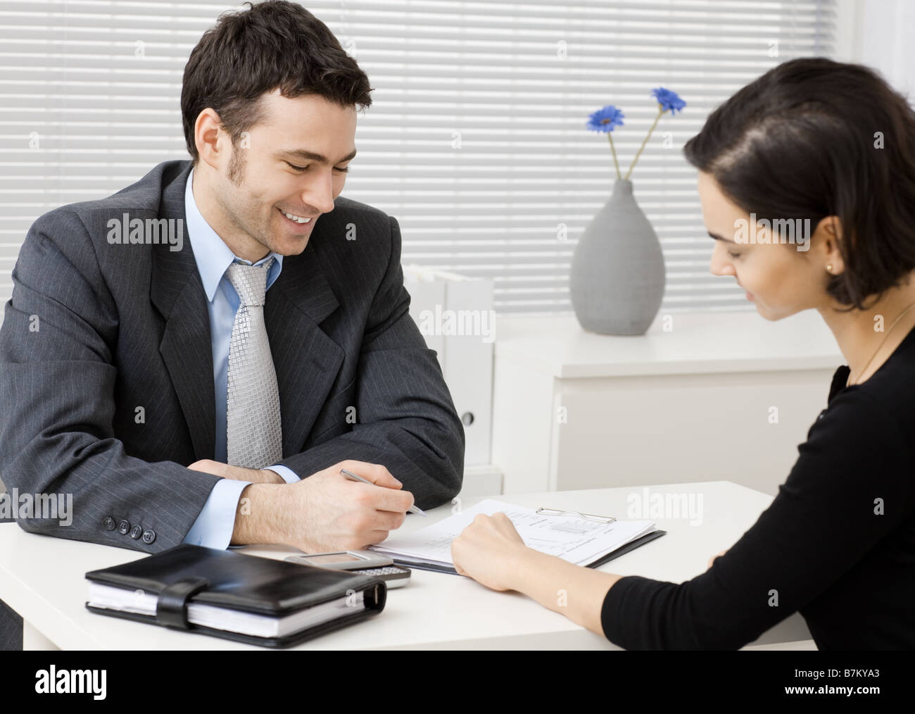 Happy young adviser businessman consulting at office smiling - Stock Image