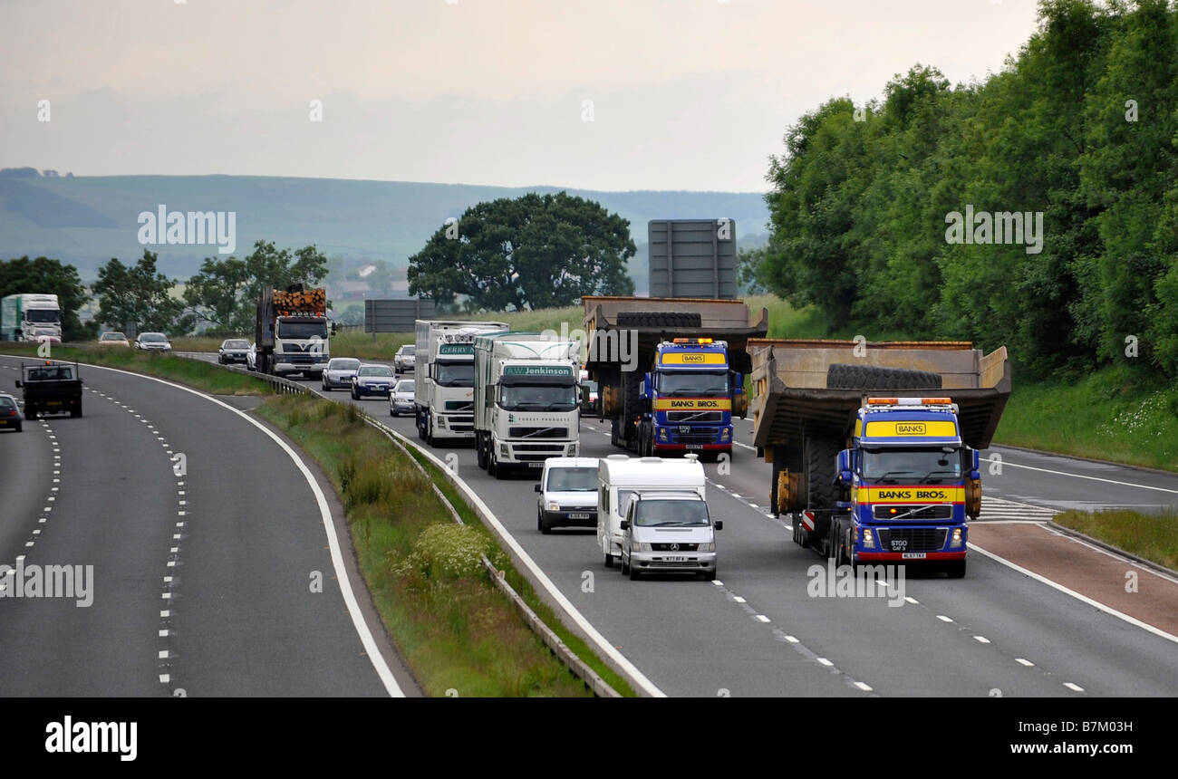 Heavy haulage truck carrying a giant dump trucks wide abnormal load on the motorway - Stock Image