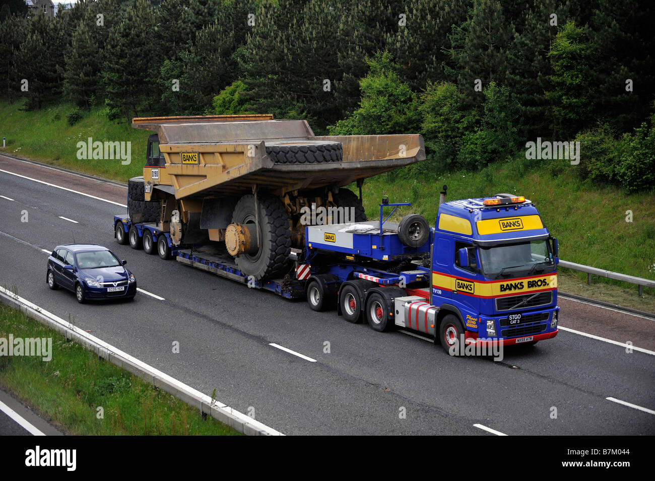 Banks Volvo FH heavy haulage truck carrying a giant dump truck wide abnormal load on the motorway - Stock Image