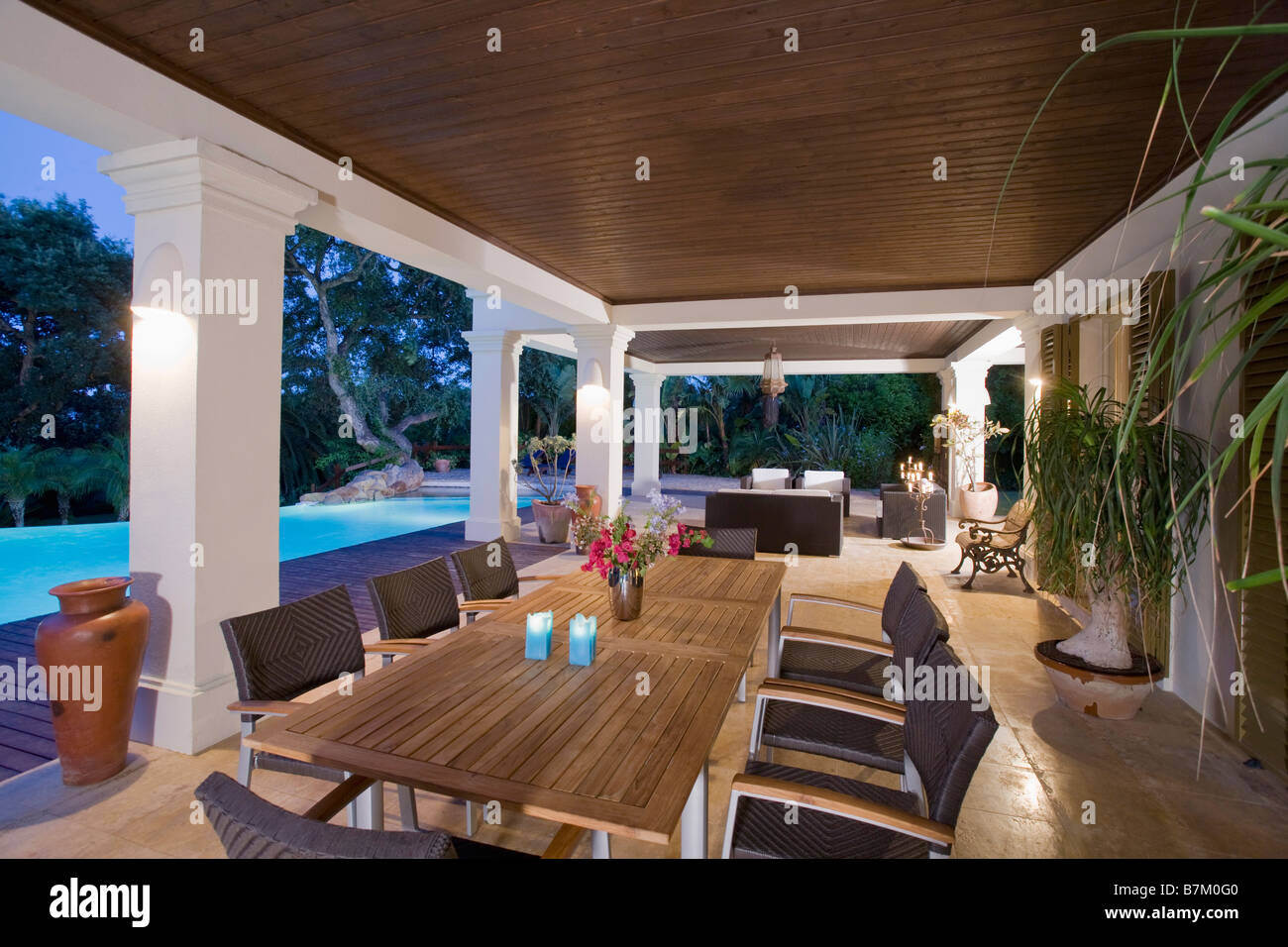 dining table and chairs on veranda beside swimming pool of modern