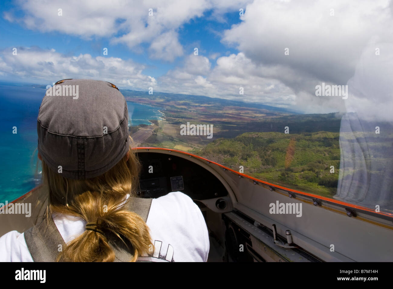 Female pilot in glider airplane flying over coastline at north coast of Oahu Hawaii - Stock Image