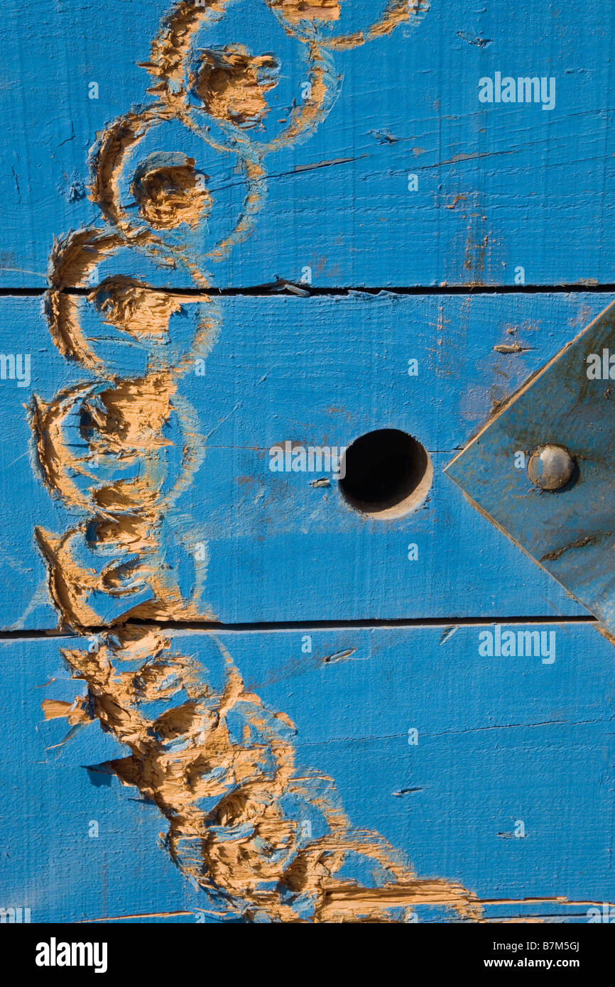 Abstract planks of wood gouged with a pattern a hole and part of a metal triangle - Stock Image