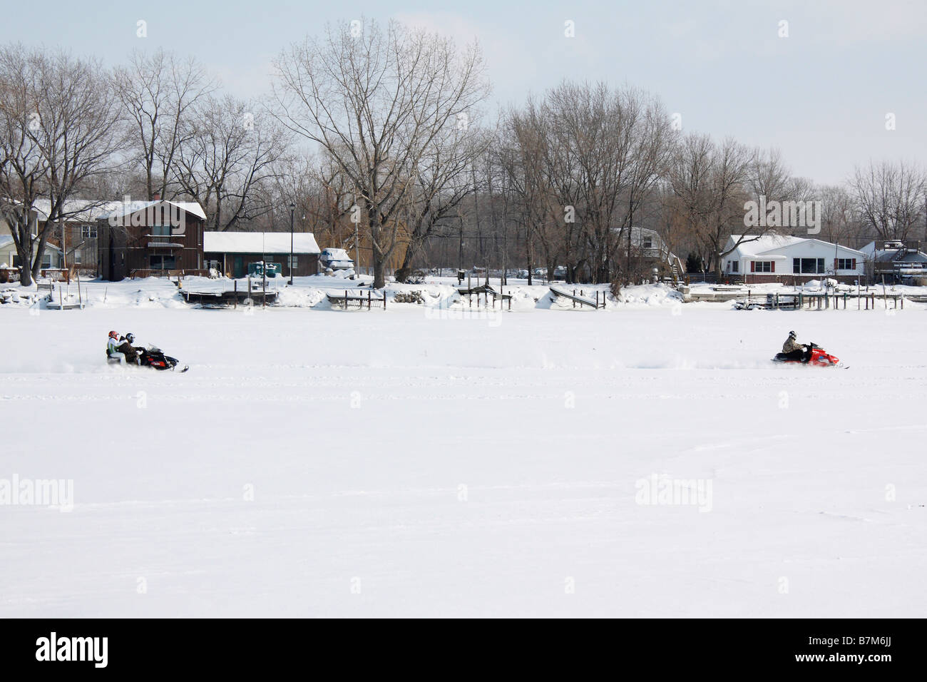 Young people snowmobiling on frozen Lake Erie in Ohio USA - Stock Image