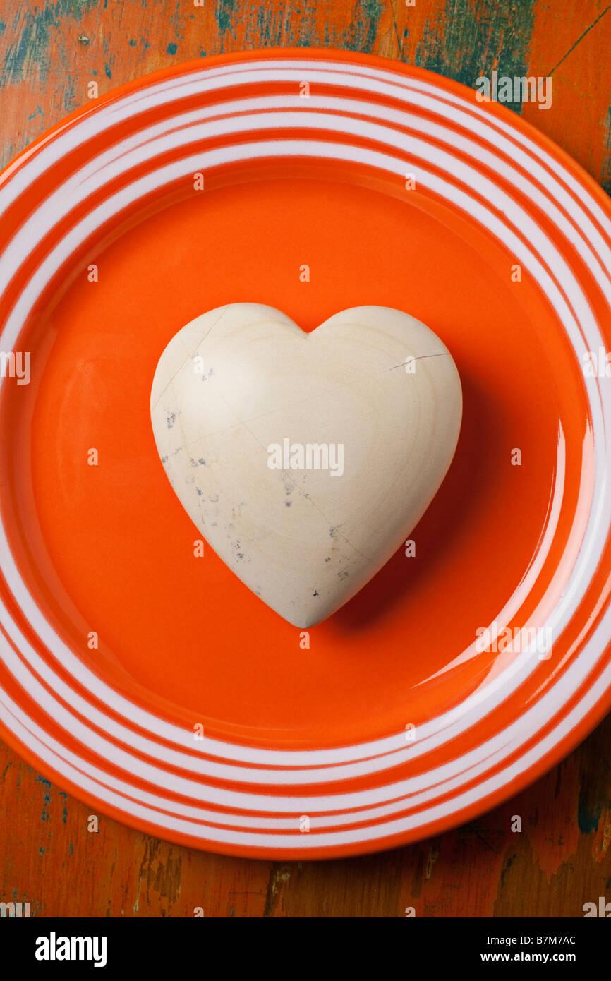White stone heart on orange plate - Stock Image