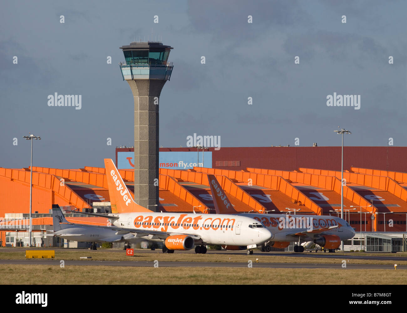 EasyJet plane taxing past the control tower at London Luton airport - Stock Image