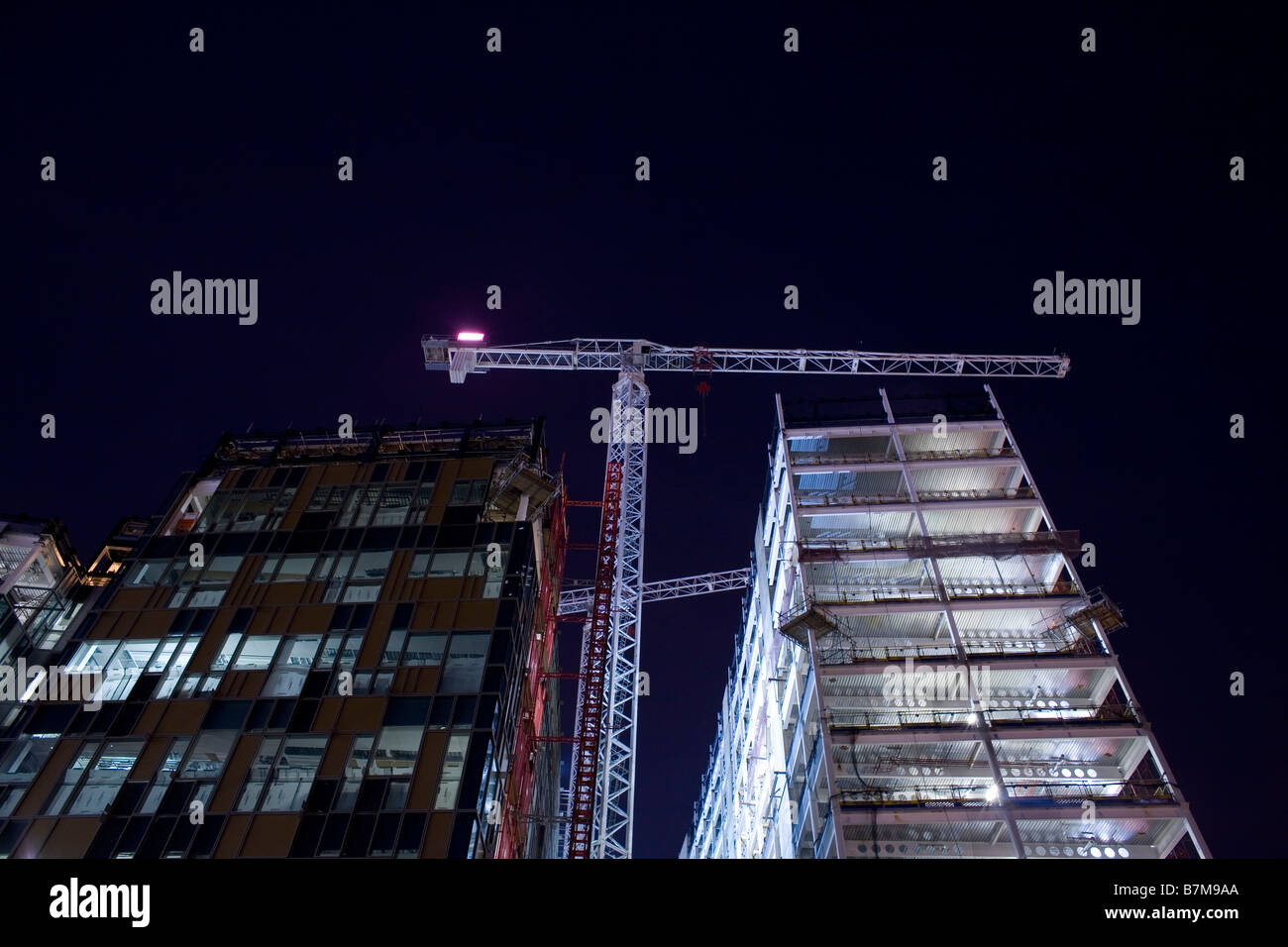 A crane stands tall between two buildings on a construction site at night in south-east London, United Kingdom. Stock Photo