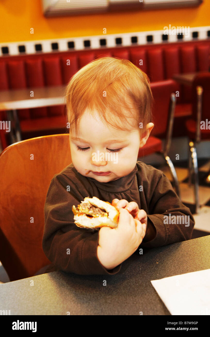 Child (15 month) old eating first Hamburger ever in a Hamburger Restaurant.