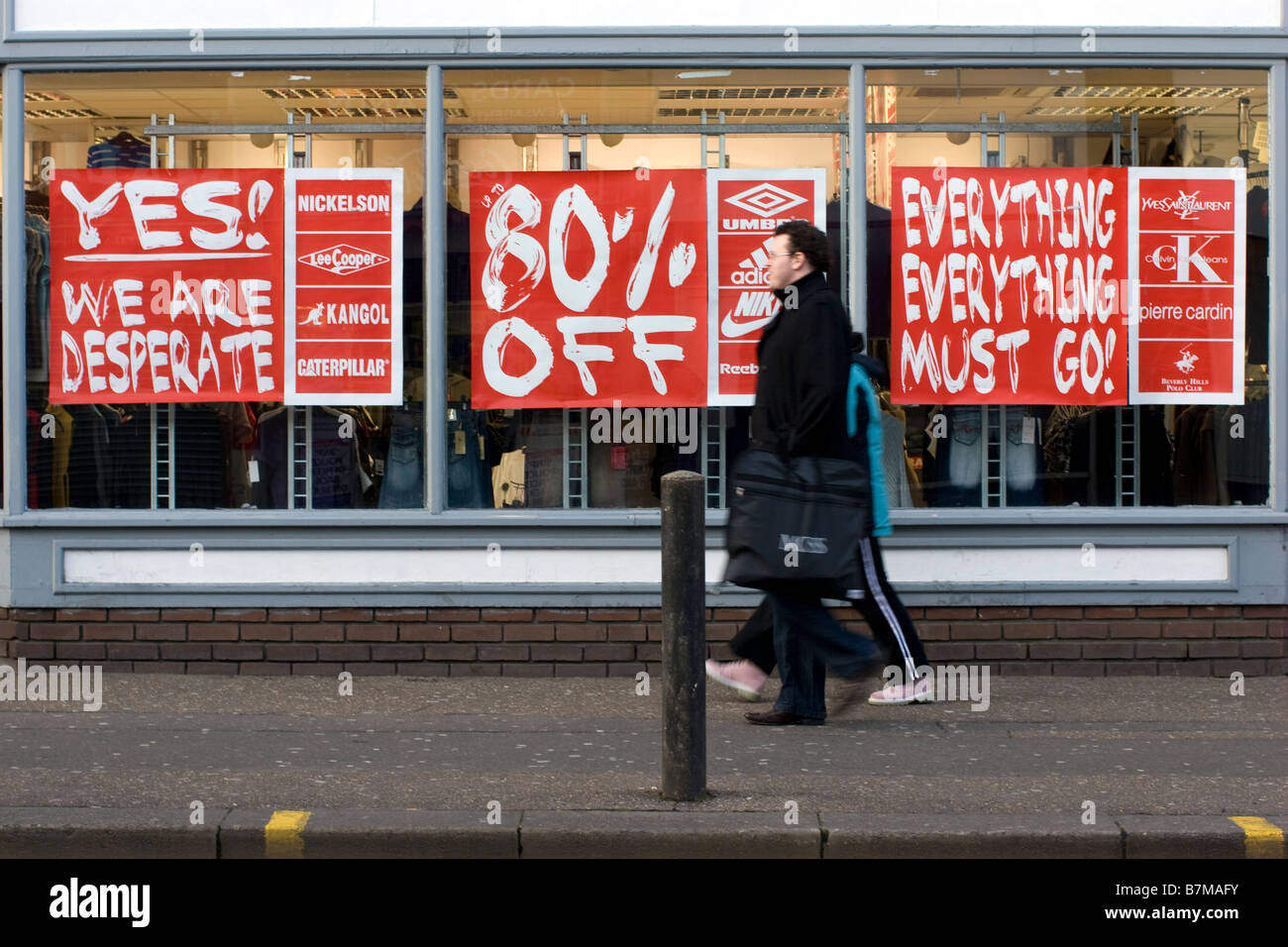 credit crunch store with 80 per cent off signs and we are desperate signs in shop window - Stock Image
