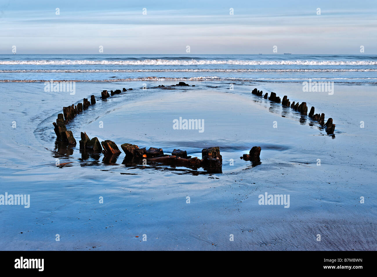 Timbers of shipwreck showing above the sand at low tide - Stock Image