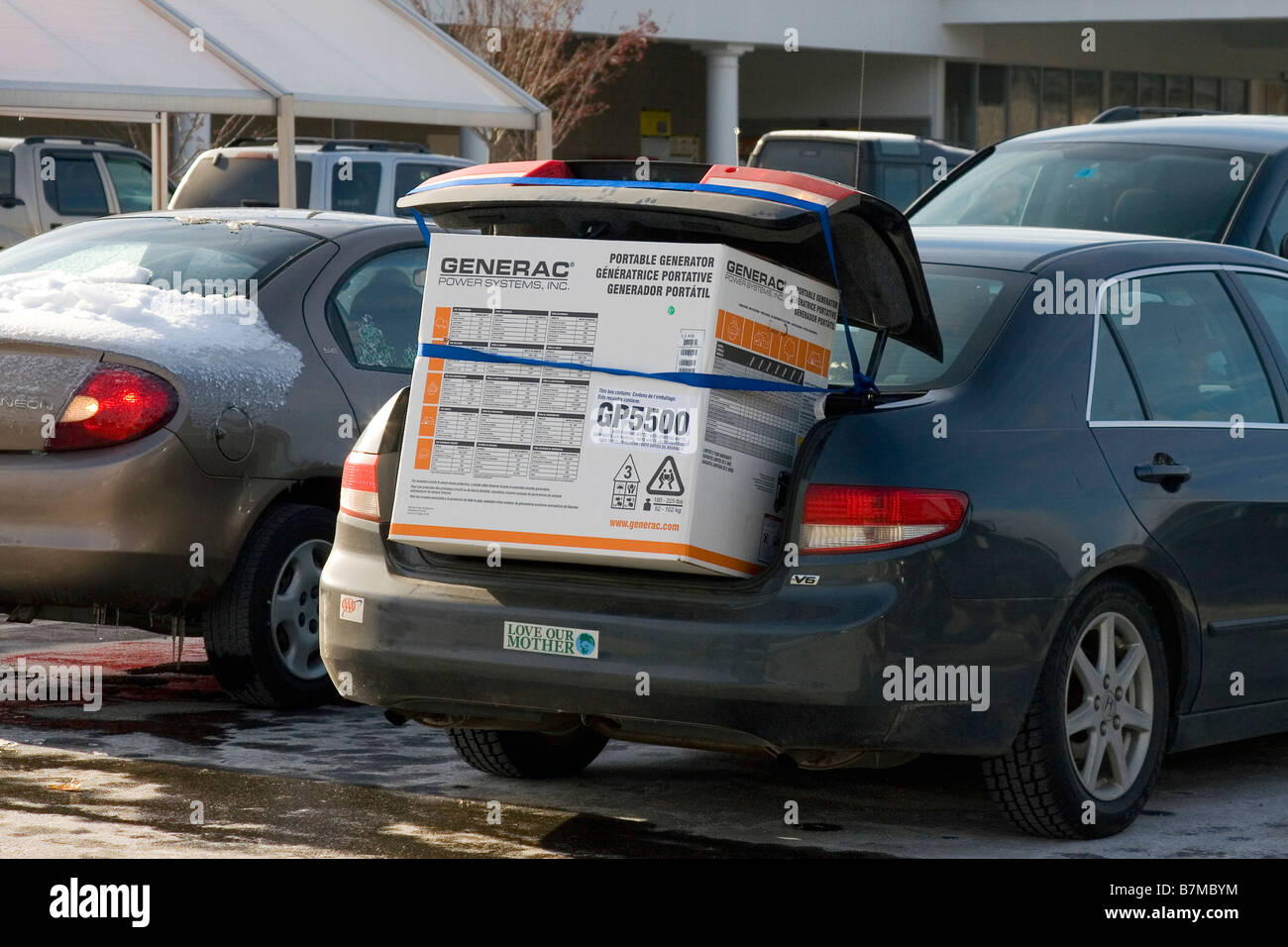 Emergency power generator loaded in the back of a car after an ice storm. - Stock Image