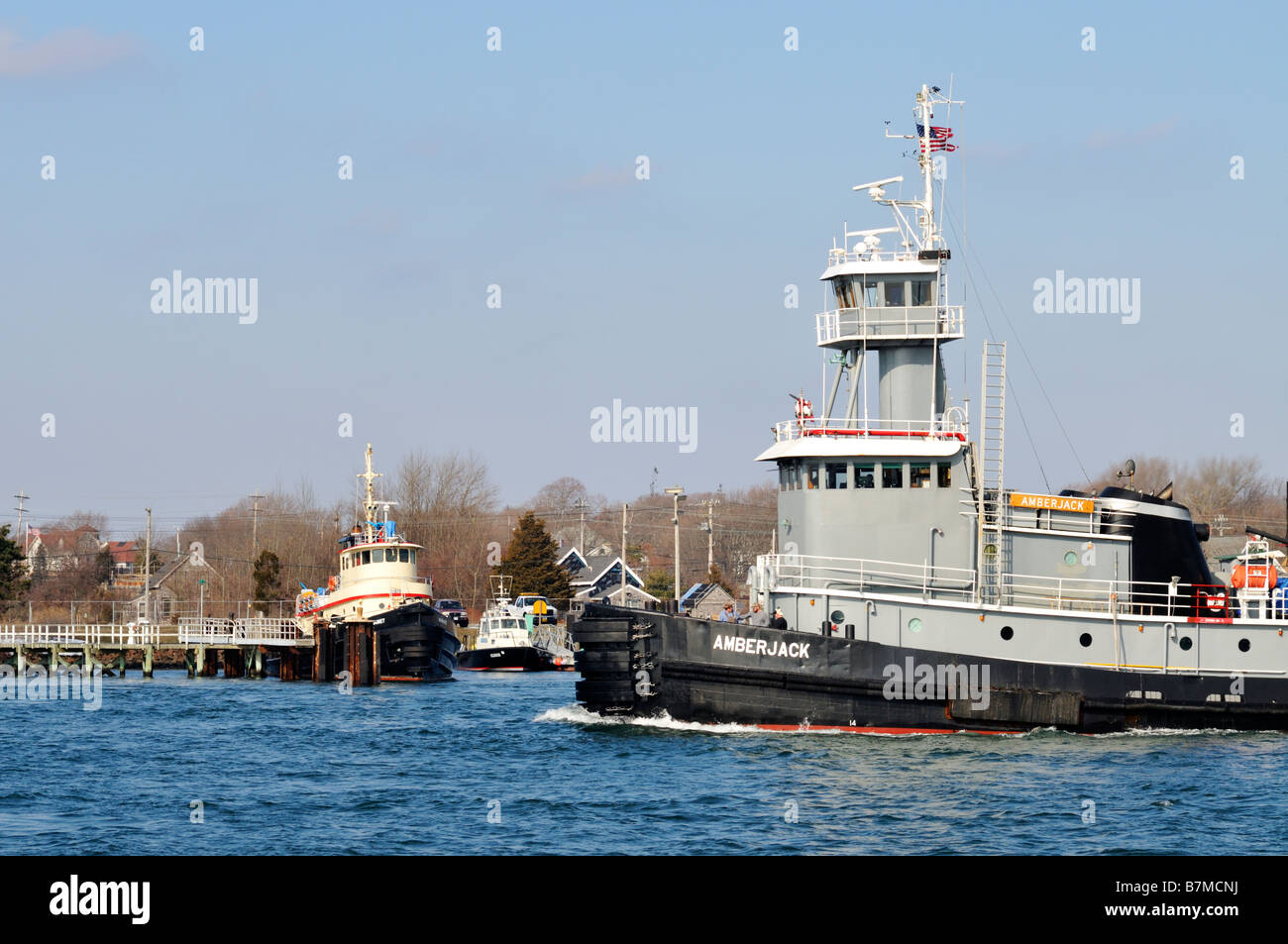 One grey tugboat passing in front of another docked tugboat - Stock Image