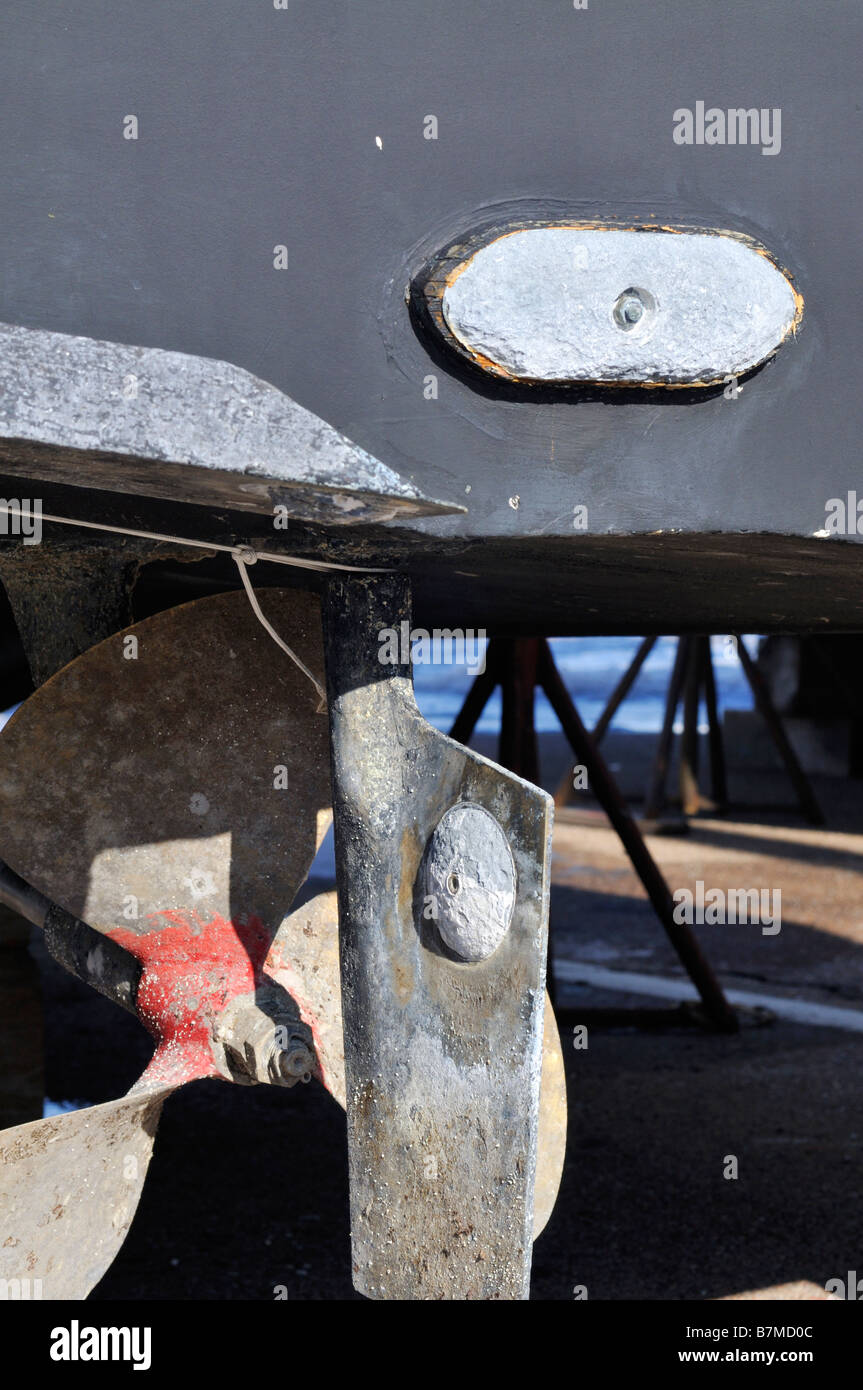 View of boat underside showing bronze prop and rudder with corrosion pitting and zincs - Stock Image