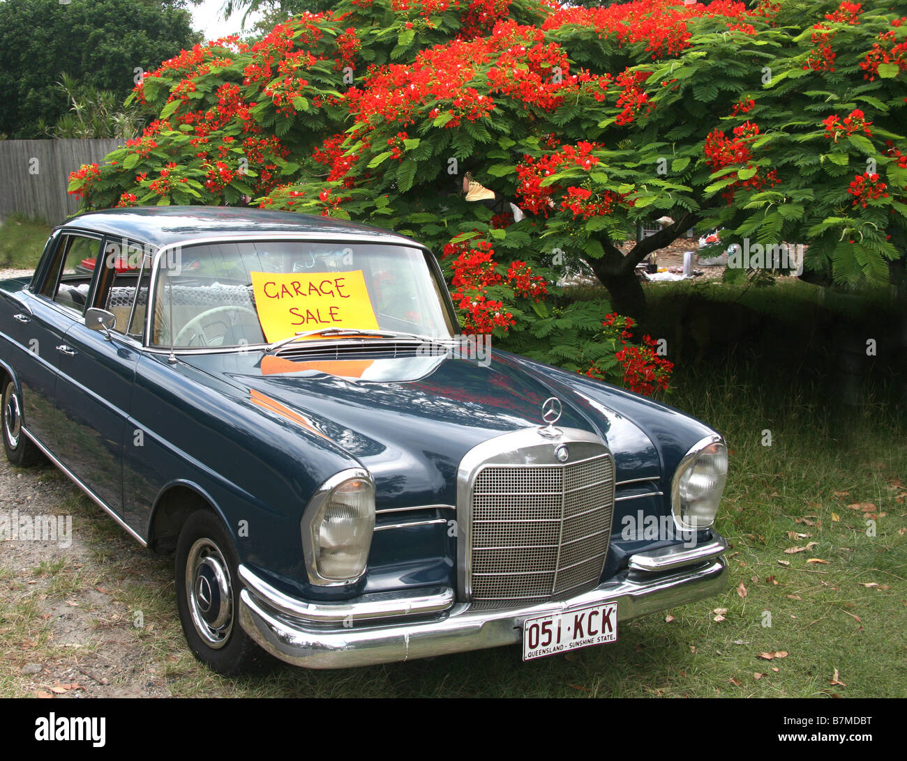 An early model Mercedes Benz displays a sign indicating a Garage Sale at Byron Bay Australia Roadside - Stock Image