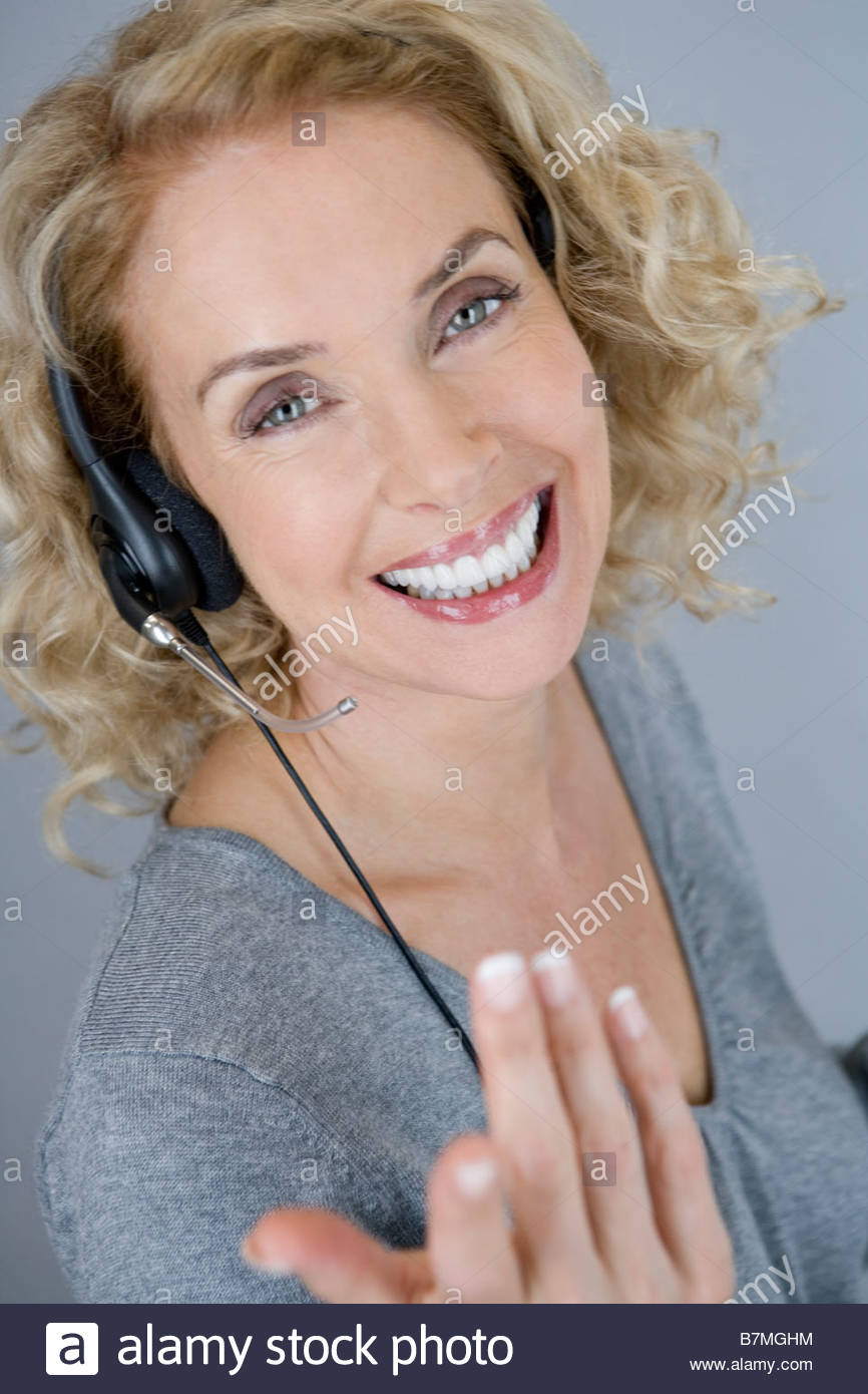 A middle aged woman wearing a headset - Stock Image