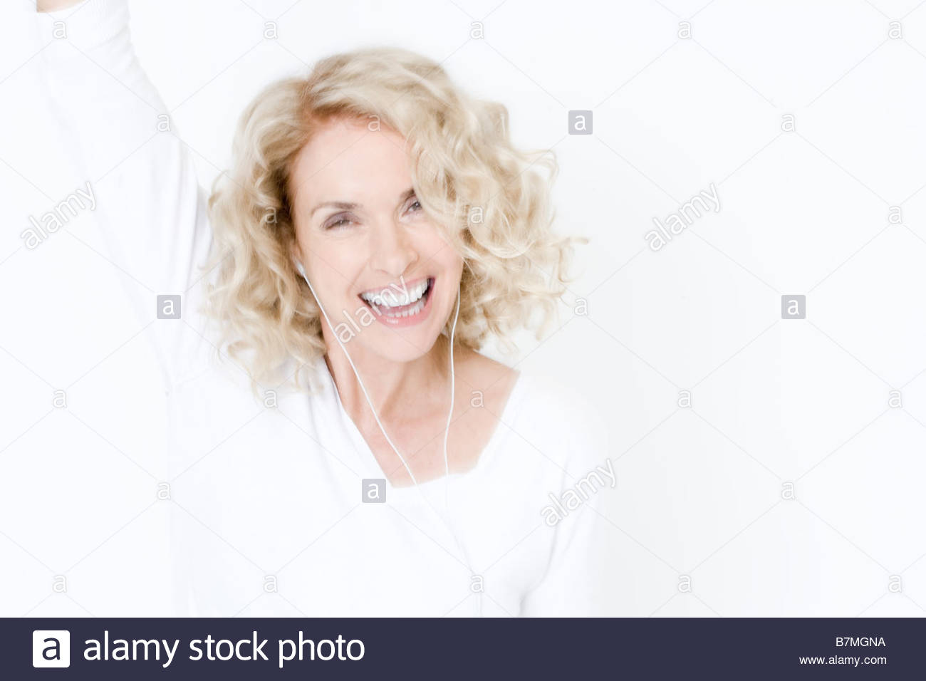 A middle-aged woman listening to mp3 music player, dancing - Stock Image