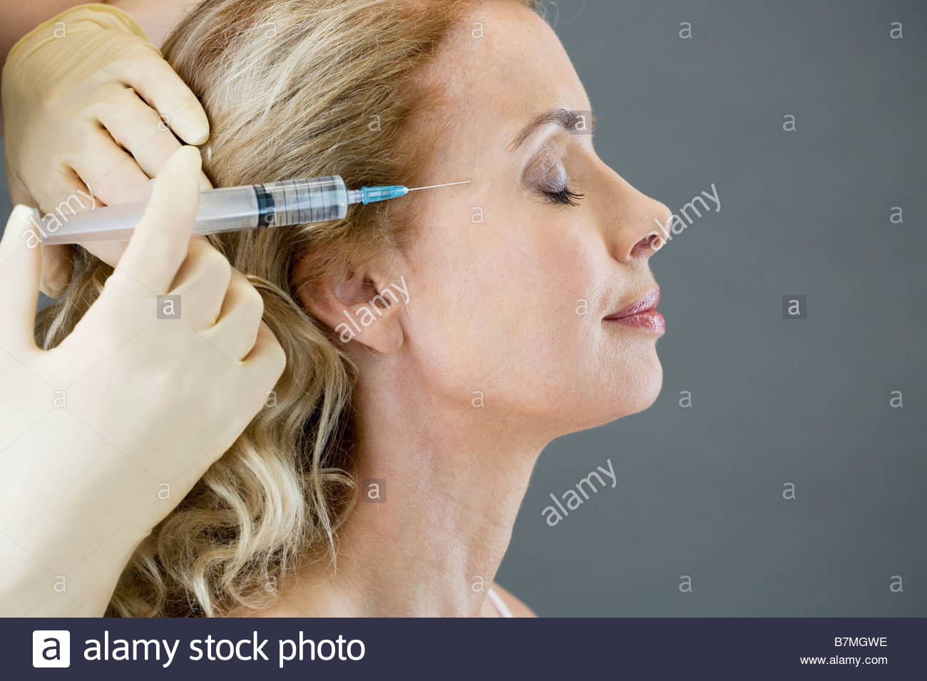 A middle-aged woman receiving a botox injection - Stock Image