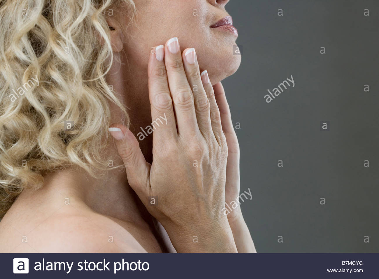 A middle-aged woman looking at her face in the mirror - Stock Image