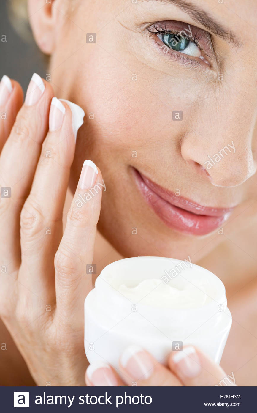 A middle-aged woman holding a pot of moisturising cream - Stock Image
