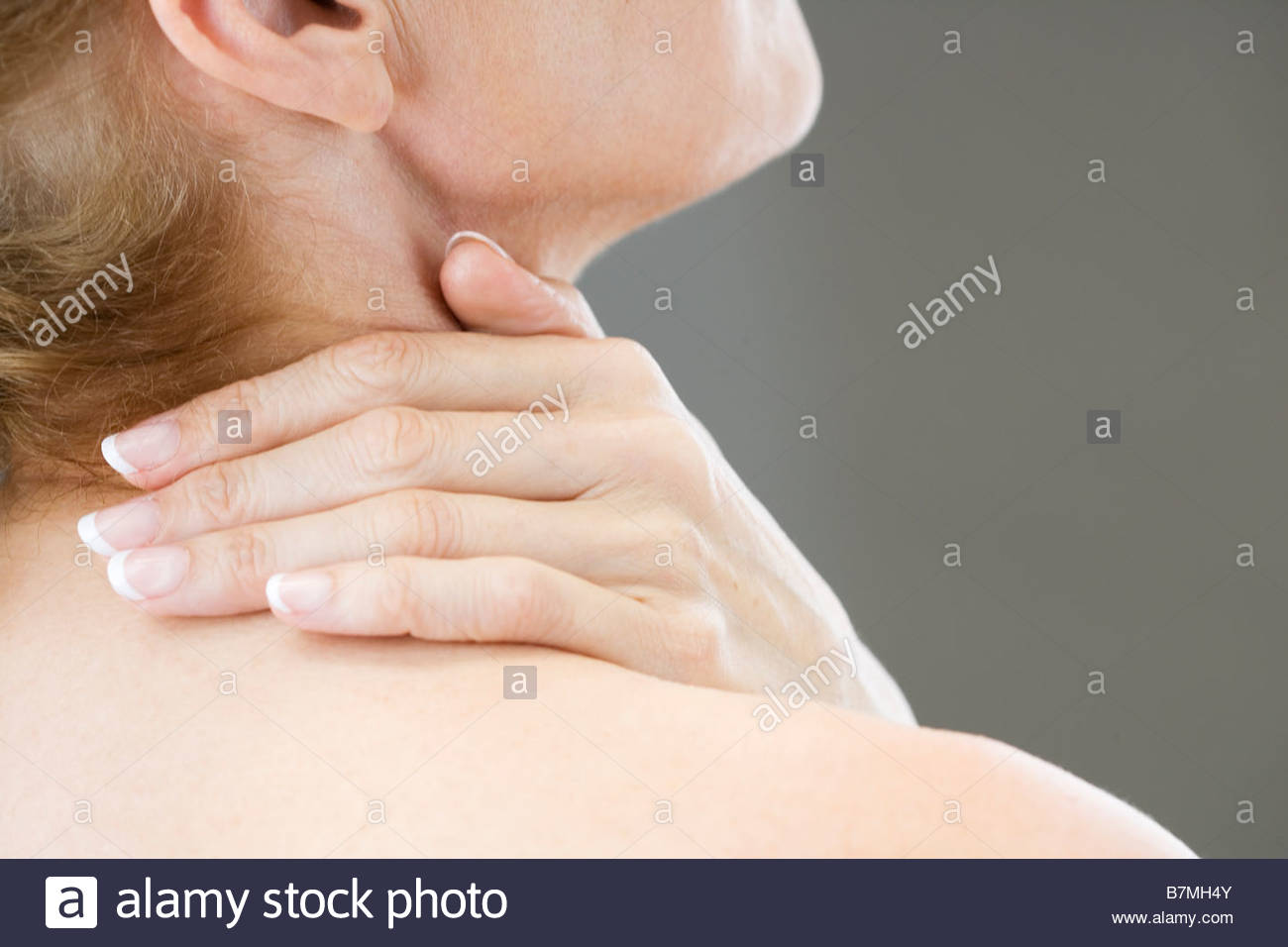 A woman with neck tension or backache - Stock Image