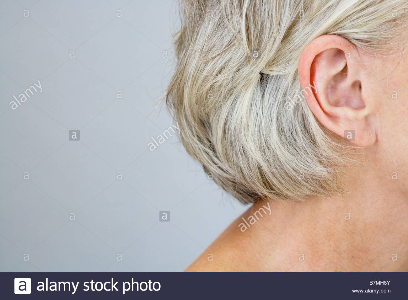 A senior woman showing her right ear and neck - Stock Image