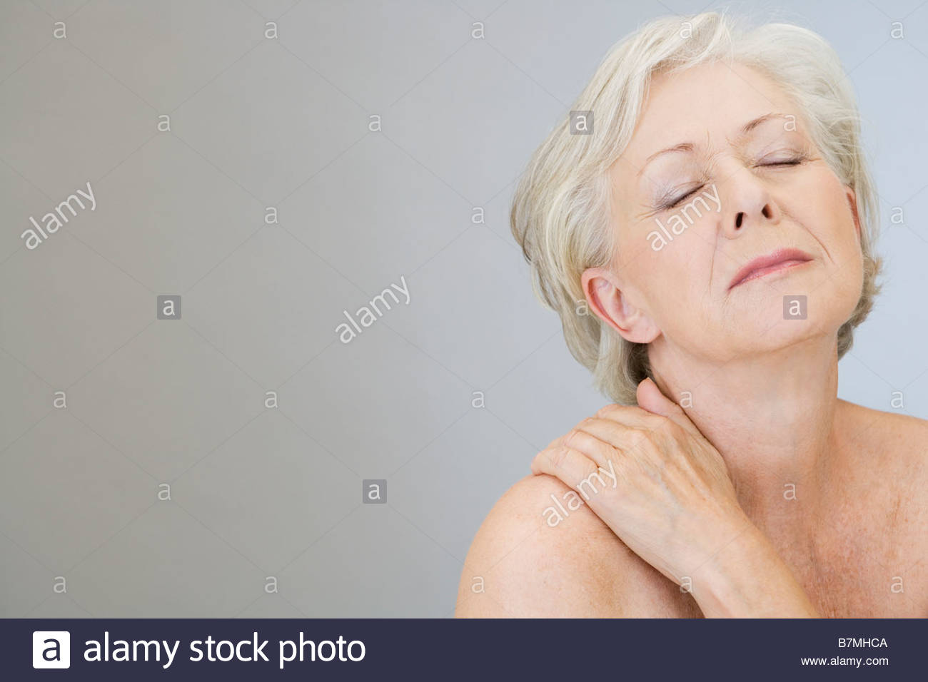 A senior woman with shoulder tension or back ache - Stock Image