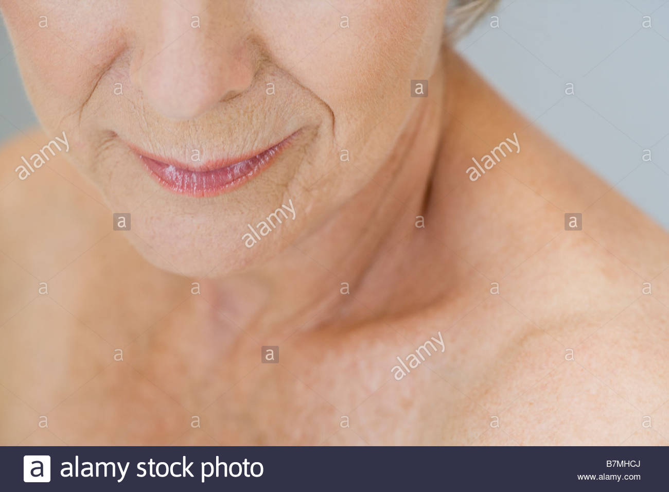 A senior woman, detail of lower half of face and shoulder - Stock Image