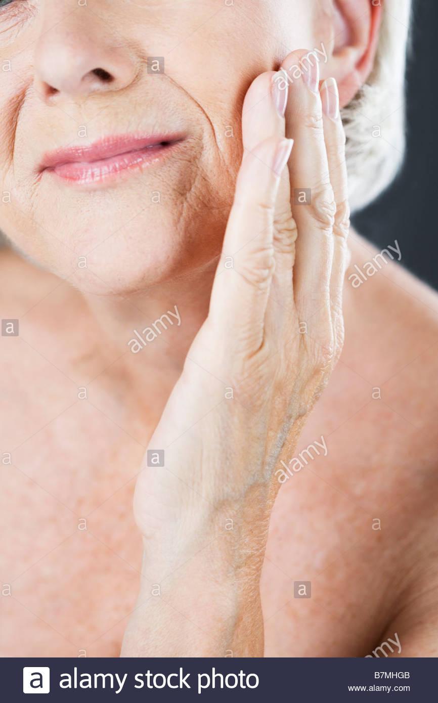 A senior woman touching her cheek - Stock Image