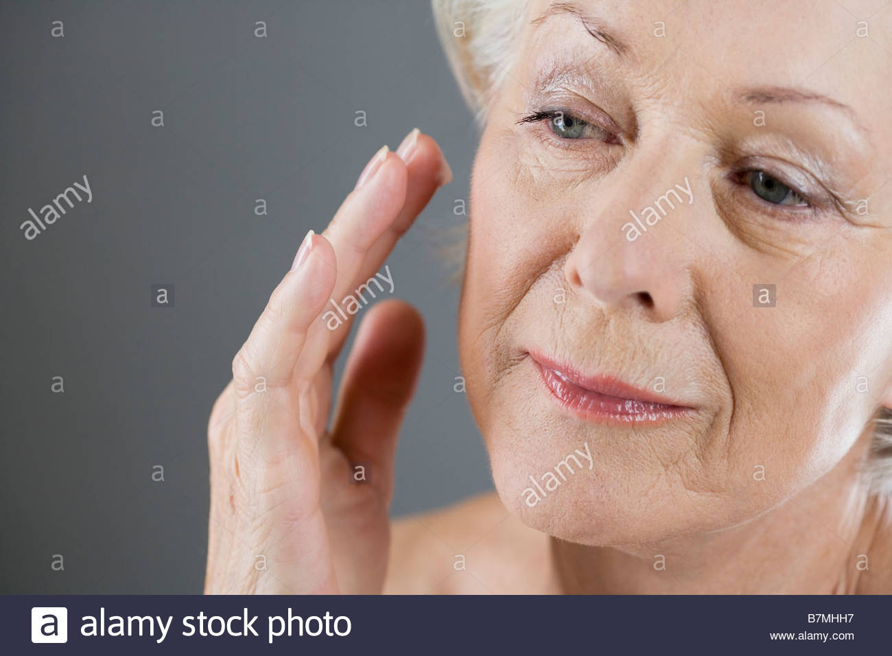 A senior woman applying moisturiser to her face - Stock Image