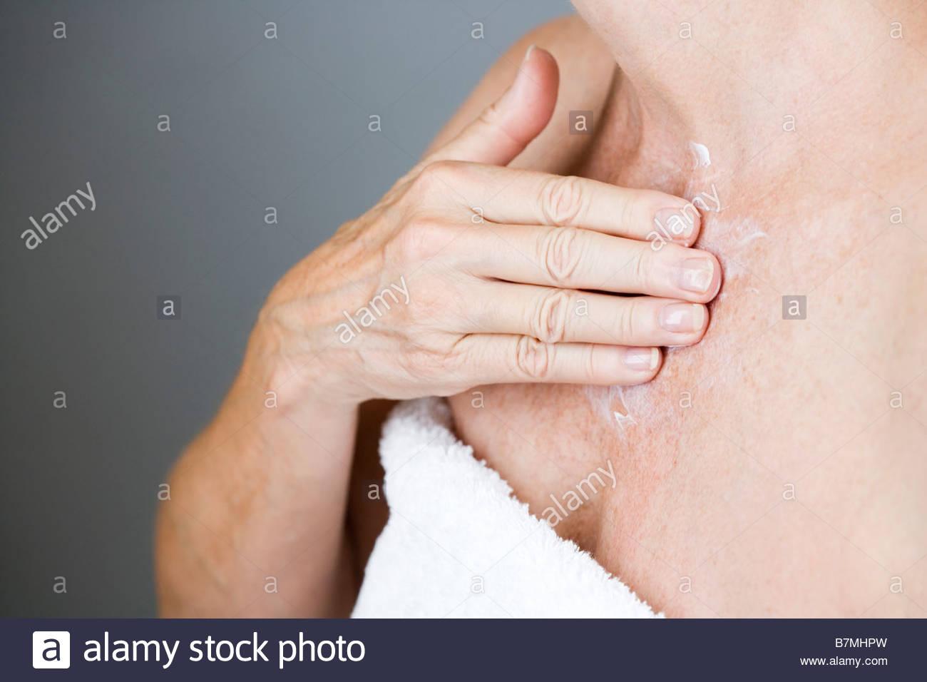 A senior woman applying moisturising cream to her chest - Stock Image
