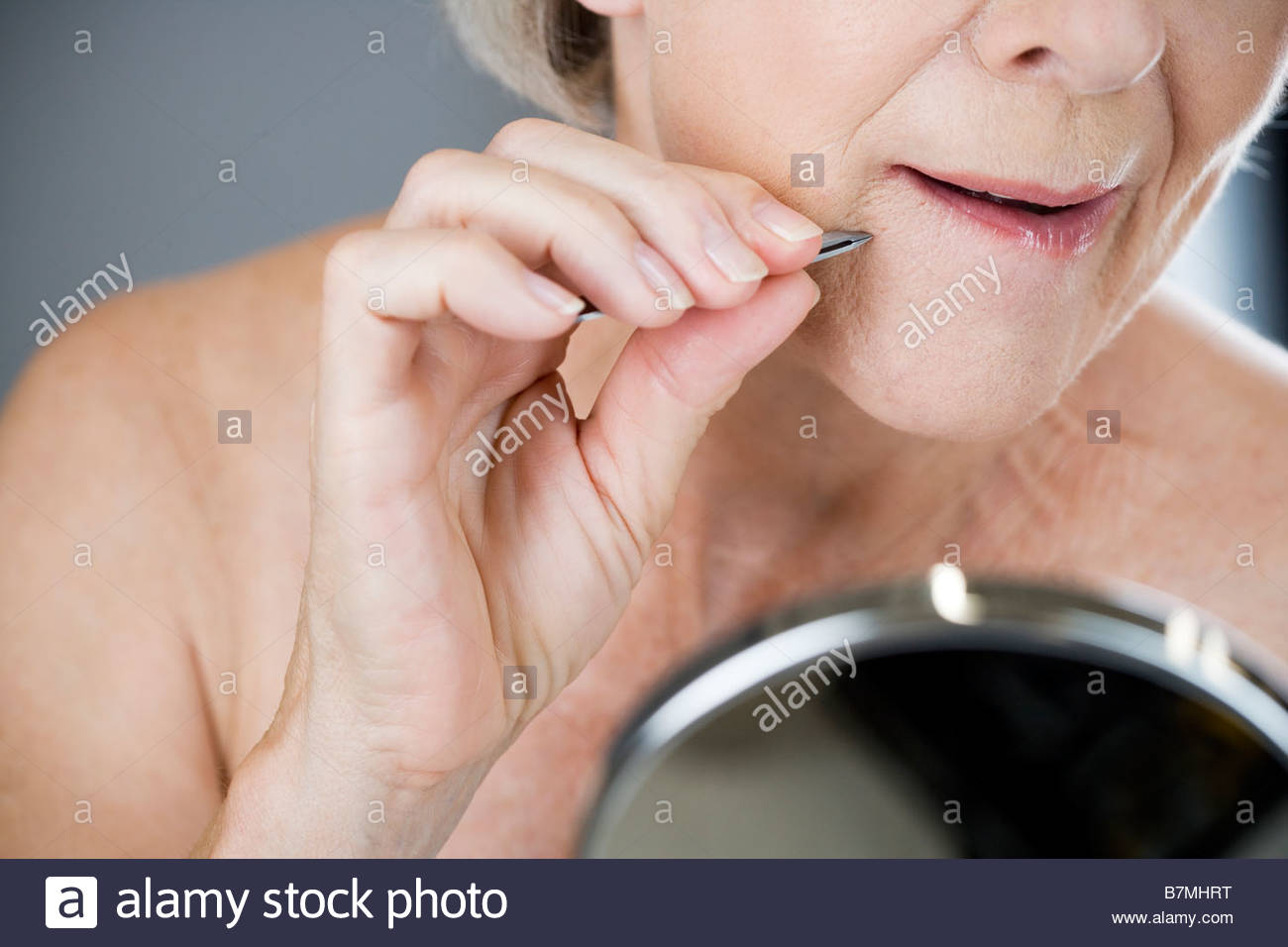 A senior woman plucking hairs from her chin with tweezers - Stock Image