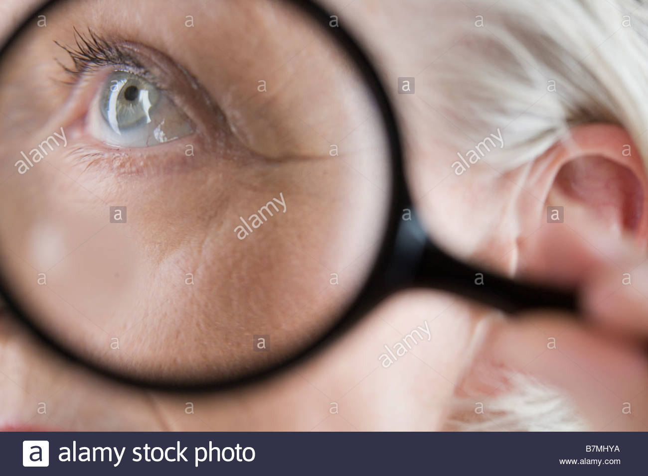 A senior woman looking through magnifying glass - Stock Image