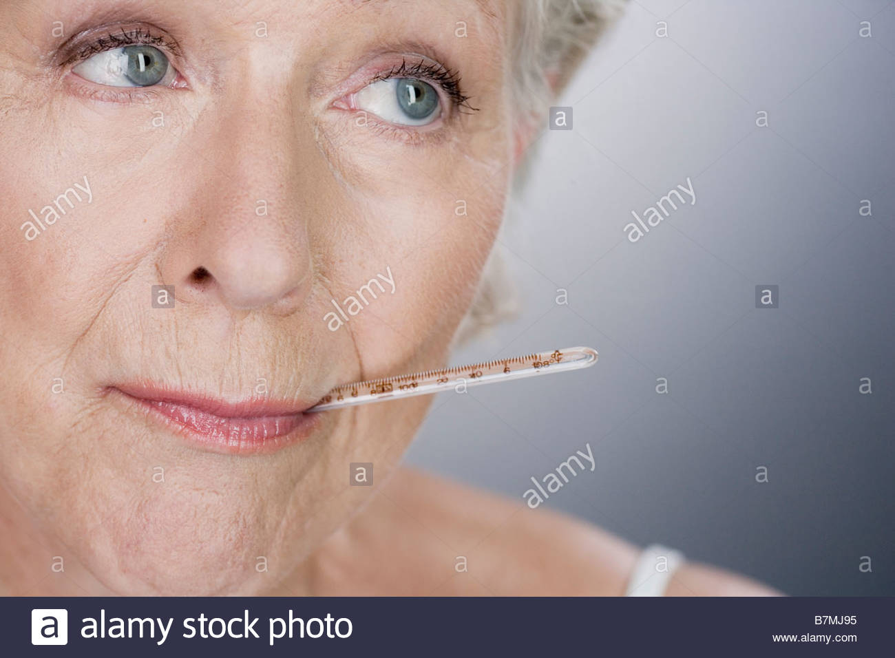 A senior woman with a thermometer in her mouth - Stock Image