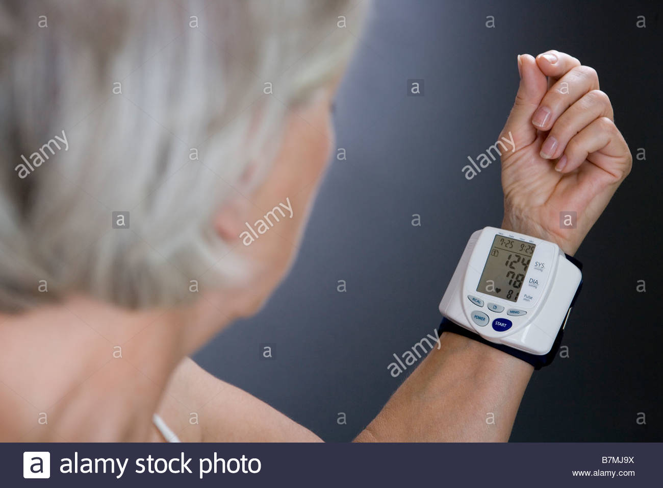 A senior woman with a heart rate monitor on her wrist - Stock Image