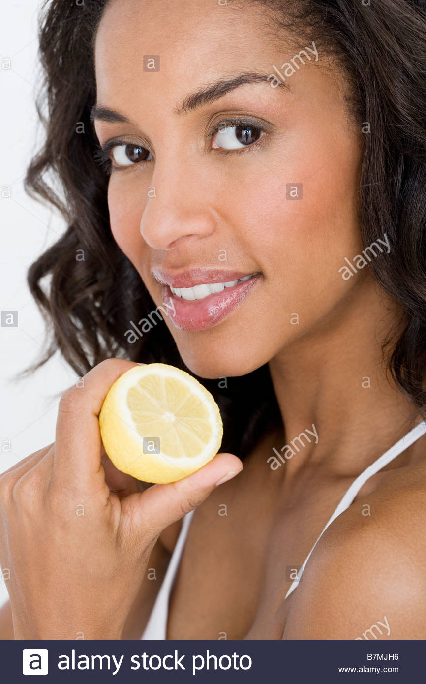 A young woman holding half a lemon - Stock Image