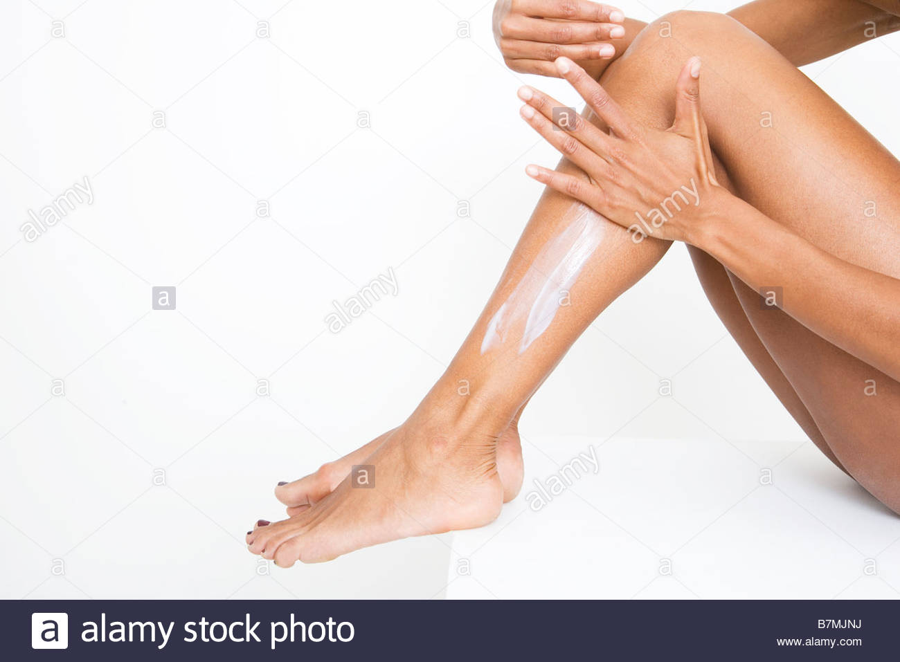 A woman applying moisturiser to her legs - Stock Image