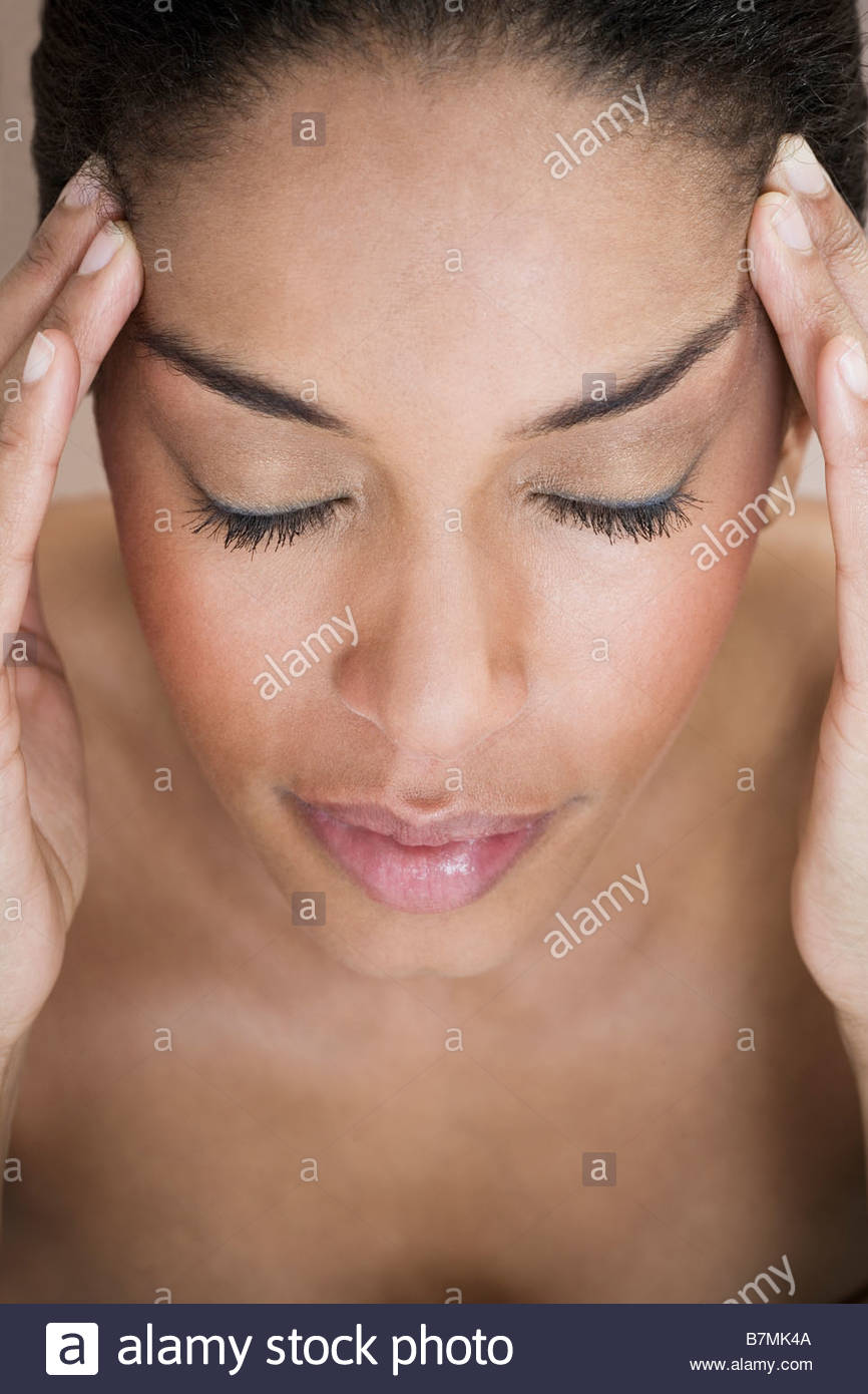 A woman with her fingers resting on her temples - Stock Image