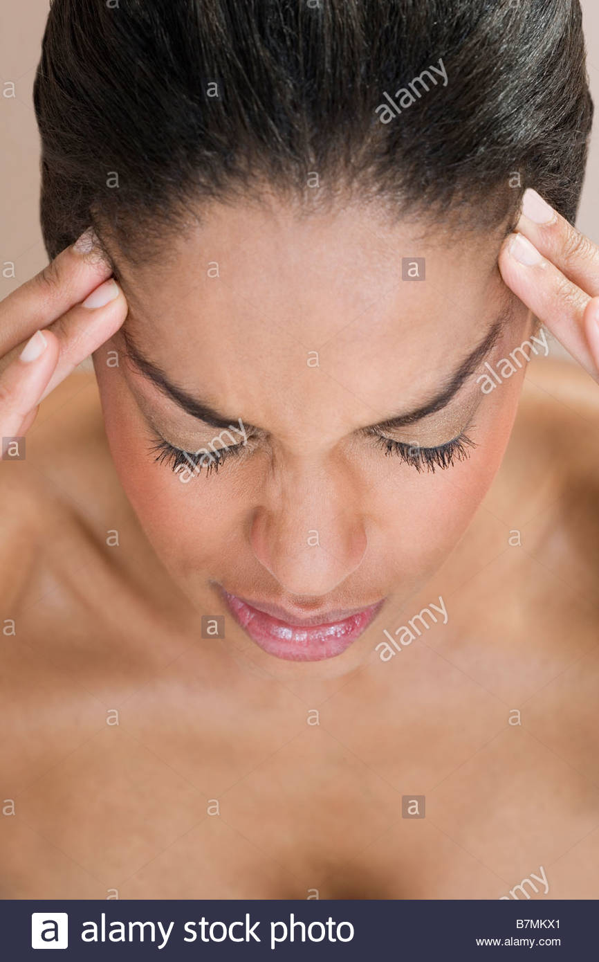 A woman with a migraine, fingers pressed to forehead - Stock Image