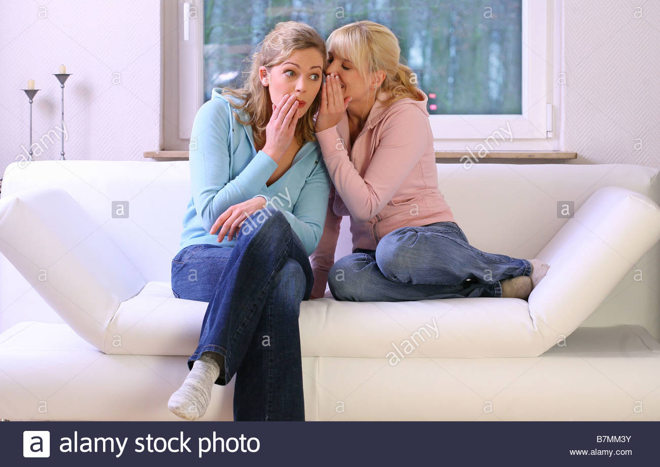 two women sitting on a white sofa talking about secrets - Stock Image