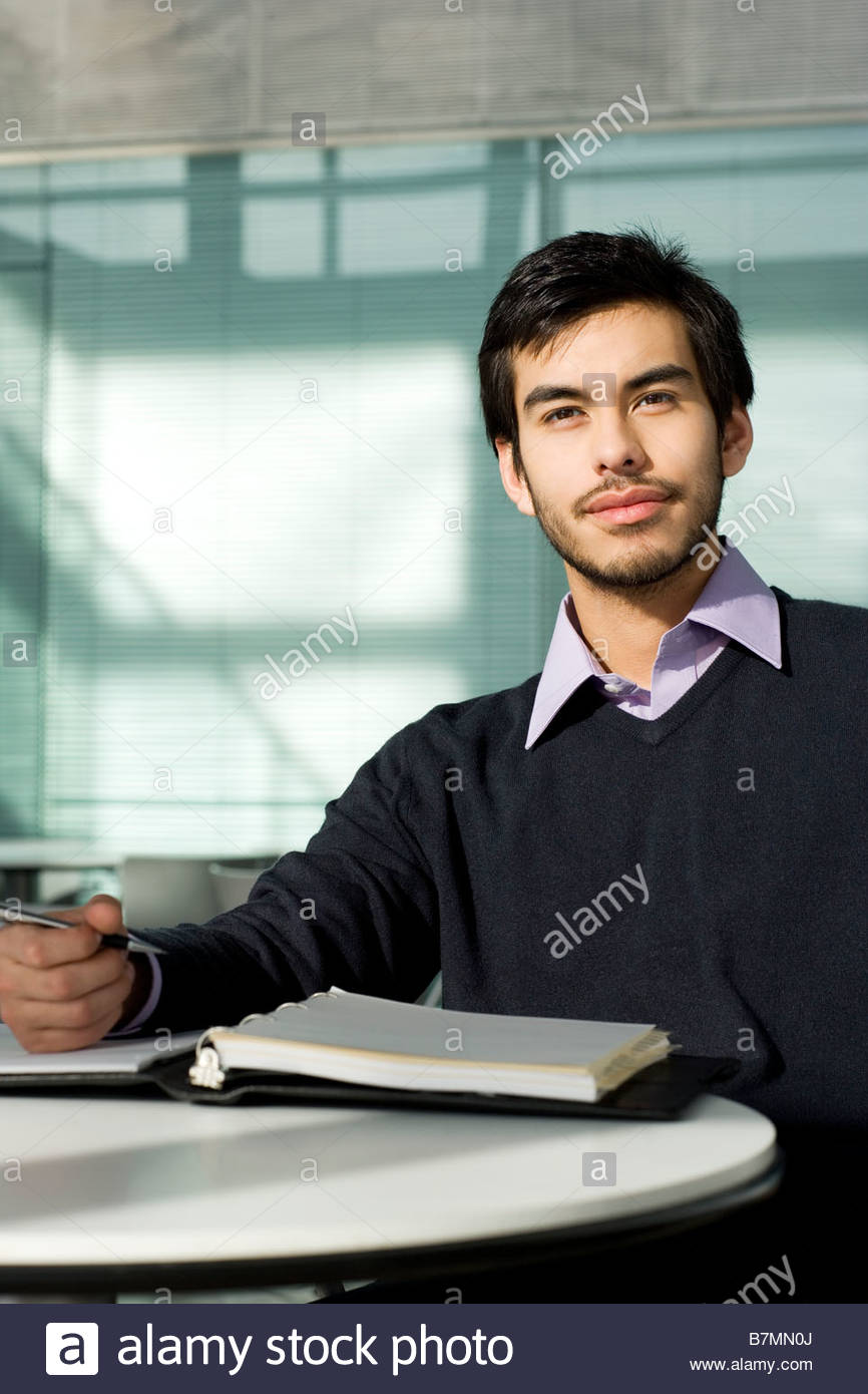 A man in an office, writing in a ledger or appointments diary - Stock Image